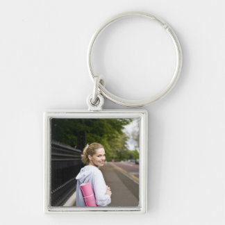 A mid adult woman carrying a yoga mat, walking Silver-Colored square key ring