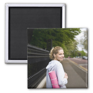 A mid adult woman carrying a yoga mat, walking square magnet