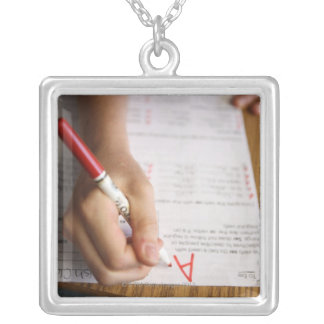 A middle school teacher puts a grade on a silver plated necklace