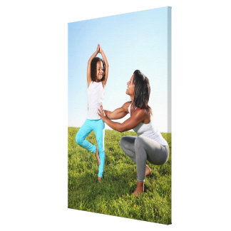 A mom helps her five-year-old girl with a yoga canvas print