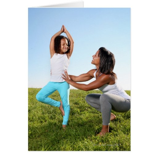 A mom helps her five-year-old girl with a yoga card