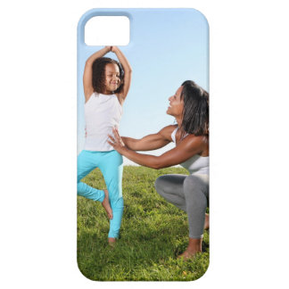 A mom helps her five-year-old girl with a yoga iPhone 5 covers
