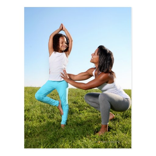 A mom helps her five-year-old girl with a yoga post cards
