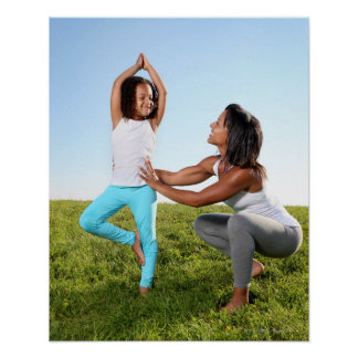 A mom helps her five-year-old girl with a yoga poster