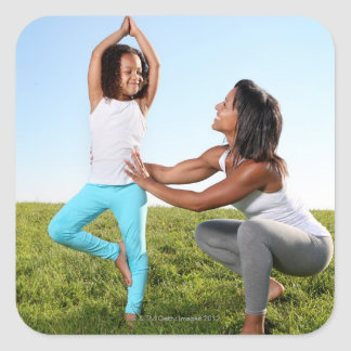 A mom helps her five-year-old girl with a yoga square sticker