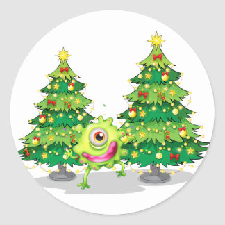 A monster dancing in front of the christmas trees round sticker