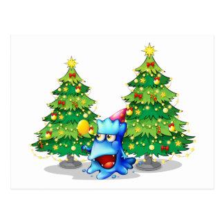A monster near the green pine christmas trees postcard