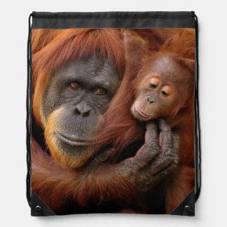 A mother and baby orangutan share a hug. drawstring bag