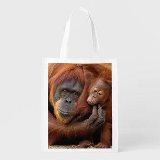 A mother and baby orangutan share a hug. reusable grocery bag