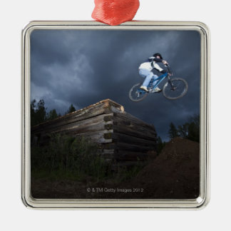 A mountain biker jumps off a log cabin in Idaho. Christmas Ornament