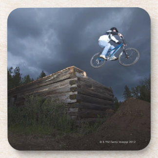 A mountain biker jumps off a log cabin in Idaho. Drink Coasters