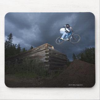 A mountain biker jumps off a log cabin in Idaho. Mouse Mat