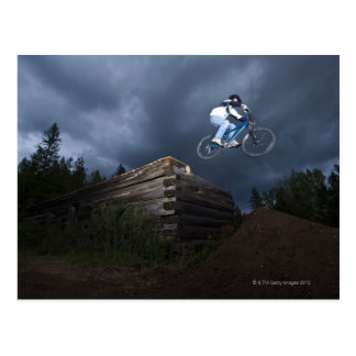 A mountain biker jumps off a log cabin in Idaho. Postcard