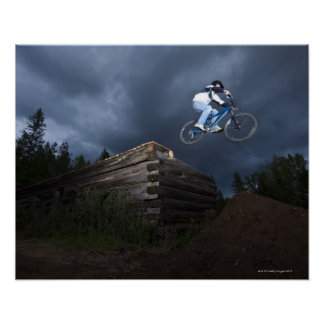 A mountain biker jumps off a log cabin in Idaho. Poster