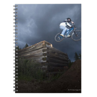 A mountain biker jumps off a log cabin in Idaho. Spiral Notebook