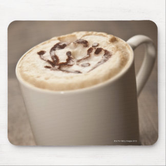 A mug of Cappuccino coffee topped with melted Mouse Pad
