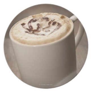 A mug of Cappuccino coffee topped with melted Plate