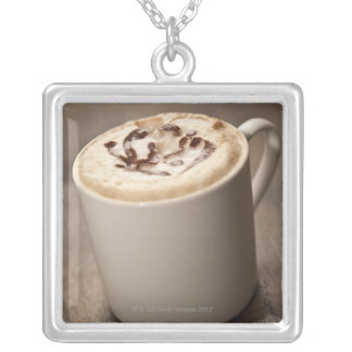 A mug of Cappuccino coffee topped with melted Silver Plated Necklace