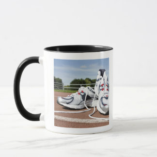 A pair of new white running trainers are placed mug