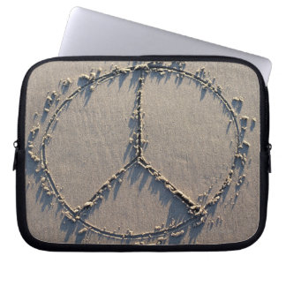 A peace sign drawn in the sand. computer sleeves