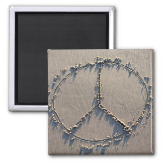 A peace sign drawn in the sand. refrigerator magnet