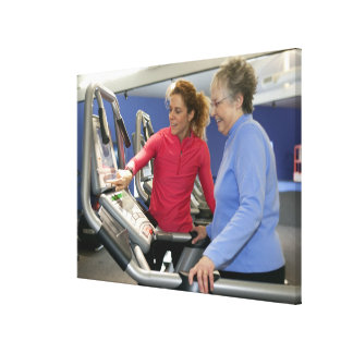 A personal trainer helps a senior woman on a canvas print