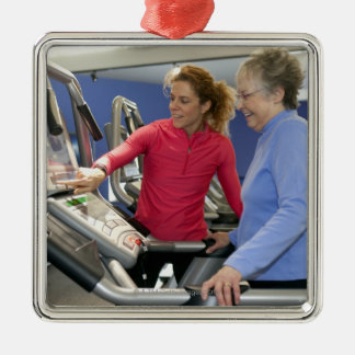 A personal trainer helps a senior woman on a Silver-Colored square decoration