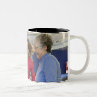 A personal trainer helps a senior woman on a Two-Tone coffee mug