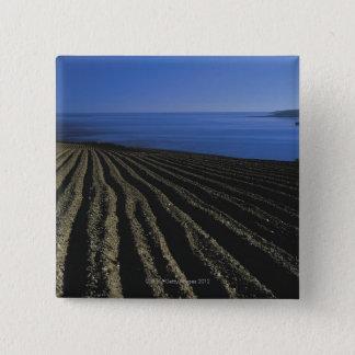 a ploughed field near the sea 15 cm square badge