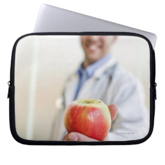 A portrait of a doctor holding a apple. laptop sleeve