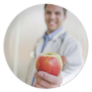 A portrait of a doctor holding a apple. plate
