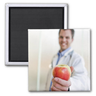 A portrait of a doctor holding a apple. square magnet