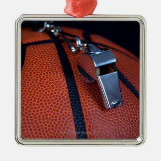 A referee s whistle rests on top of a christmas ornaments