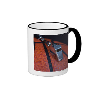A referee s whistle rests on top of a mug