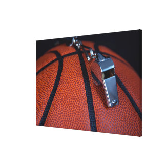 A referee's whistle rests on top of a canvas print
