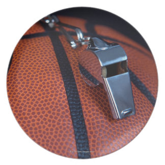 A referee's whistle rests on top of a dinner plates