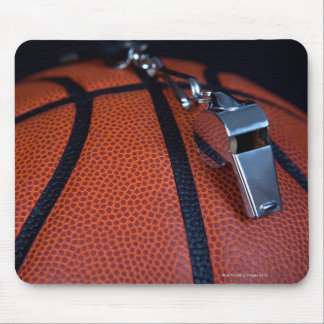A referee's whistle rests on top of a mousepad