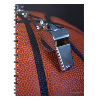 A referee's whistle rests on top of a note books