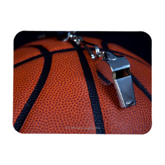 A referee's whistle rests on top of a rectangular photo magnet