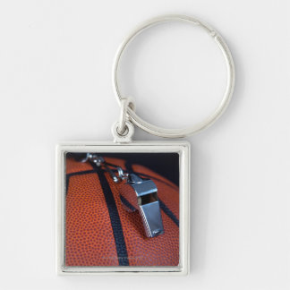 A referee's whistle rests on top of a Silver-Colored square key ring