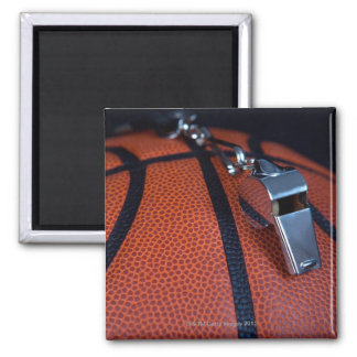 A referee's whistle rests on top of a square magnet