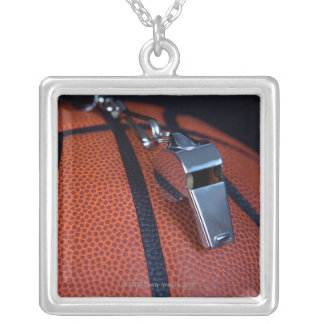 A referee's whistle rests on top of a square pendant necklace