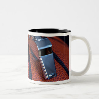 A referee's whistle rests on top of a Two-Tone coffee mug