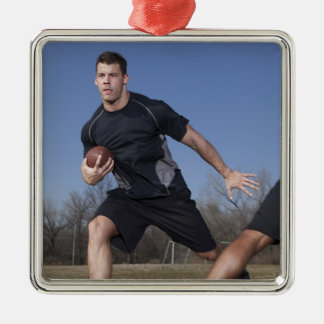 A running play during a touch football game. Silver-Colored square decoration