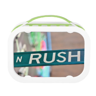 A Rush Street street sign in front of a neon Lunch Box