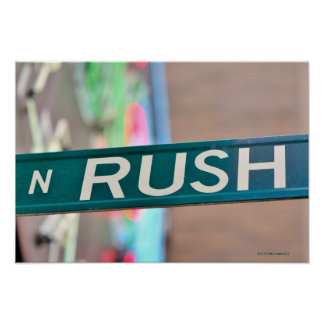 A Rush Street street sign in front of a neon Poster