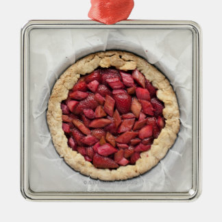 A rustic, homemade tart filled with fresh Silver-Colored square decoration