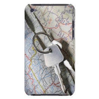 A set of car keys on a pile of road maps. iPod touch case