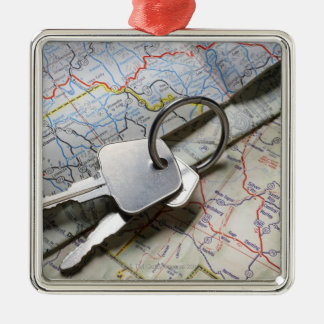 A set of car keys on a pile of road maps. Silver-Colored square decoration