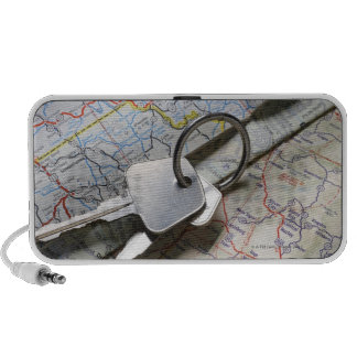 A set of car keys on a pile of road maps. travelling speaker